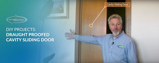 ecoMaster Maurice Beinat standing in front of a cavity sliding door